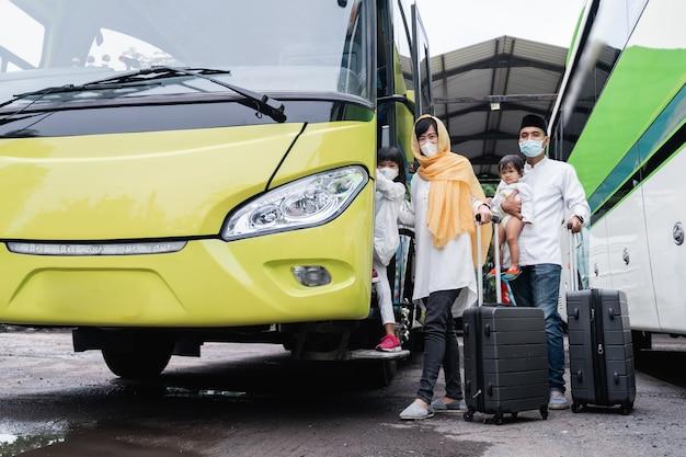 Felice viaggio di vacanza musulmana asiatica in sella a un autobus insieme alla famiglia che indossa la maschera per prevenire la diffusione del virus
