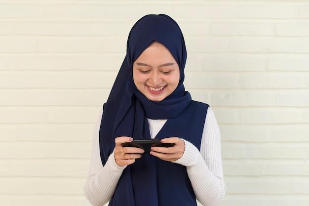 Felice donna musulmana asiatica entusiasta di giocare sul suo smart phone