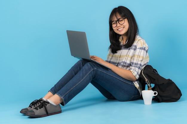Felice studente asiatico seduto con l'utilizzo di laptop su uno sfondo blu