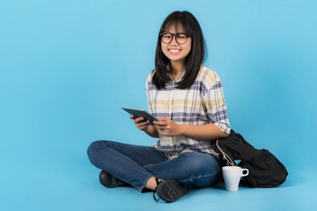 Felice studente asiatico seduto con l'utilizzo di tablet su sfondo blu