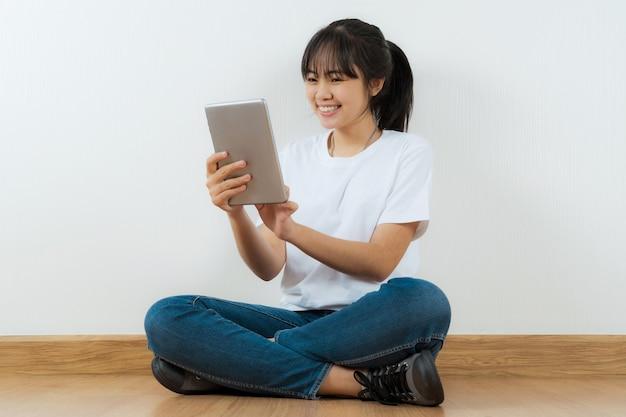 Felice studente asiatico seduto con l'utilizzo di tablet a casa sfondo