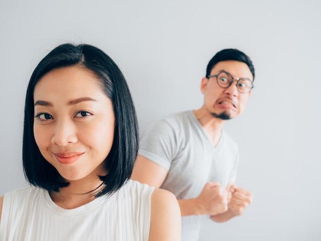 Felice moglie asiatica e marito perdente arrabbiato