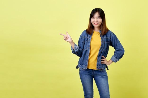 Felice donna asiatica in giacca di jeans rivolto verso il lato per copiare lo spazio e guardando la telecamera su uno spazio giallo
