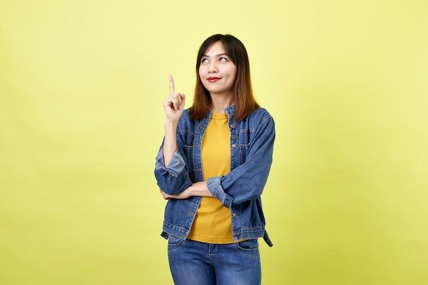 Felice donna asiatica in giacca di jeans rivolta verso l'alto per copiare lo spazio e guardando la telecamera su uno spazio giallo