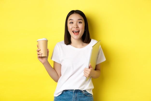 Felice donna asiatica che beve caffè e tiene in mano un laptop, salutandoti, in piedi su sfondo giallo