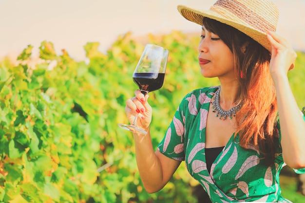 Felice donna asiatica che beve vino rosso, concetto di celebrazione
