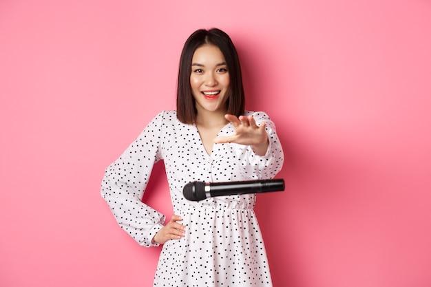 Felice donna asiatica rilascia il microfono, sorridendo e guardando fiduciosa alla telecamera, in piedi sopra il rosa.