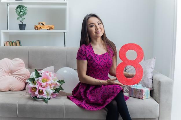 Felice donna asiatica tenendo il numero otto e seduto su un divano con presente e bouquet di fiori sorridendo allegramente nella luce del soggiorno che celebra la giornata internazionale della donna marzo