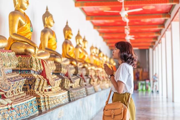 Donna asiatica felice che prega con buddha