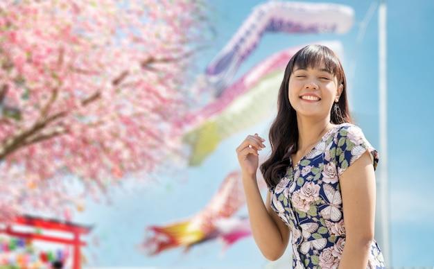 Donna asiatica felice sul festival dei fiori di sakura nel parco giapponese