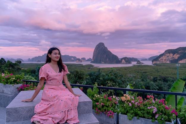 Donna asiatica felice che si siede davanti alla bella isola della montagna con il cielo crepuscolare a sametnangshe