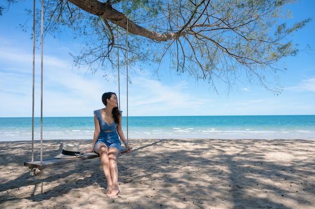 Donna asiatica felice che si siede sull'altalena di legno sulla spiaggia in mare tropicale