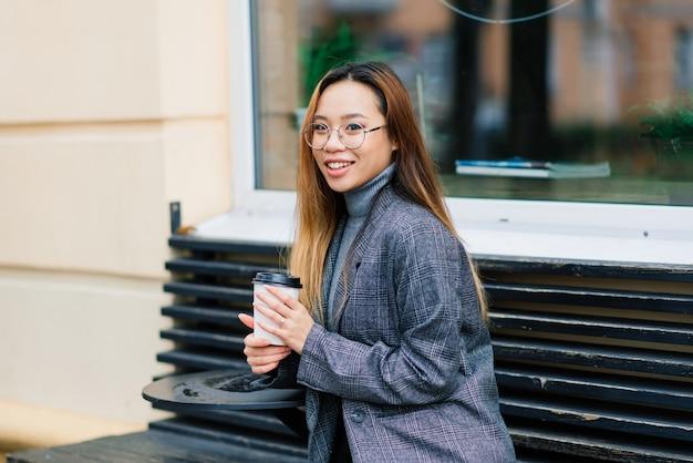Felice studentessa asiatica sulla strada della città, il concetto di educazione
