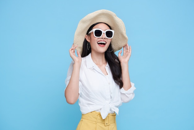 Felice donna asiatica in abiti casual estivi isolati su backgroud blu.