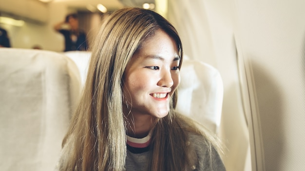 Felice donna asiatica viaggia in aereo per il turismo di vacanza