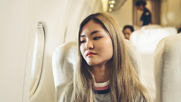 Felice donna asiatica viaggia in aereo per il turismo di vacanza.