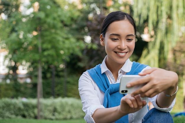 Felice donna asiatica utilizzando il telefono cellulare, tenendo selfie nel parco