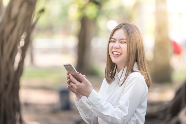 Donna asiatica felice che usando smartphone e ridendo