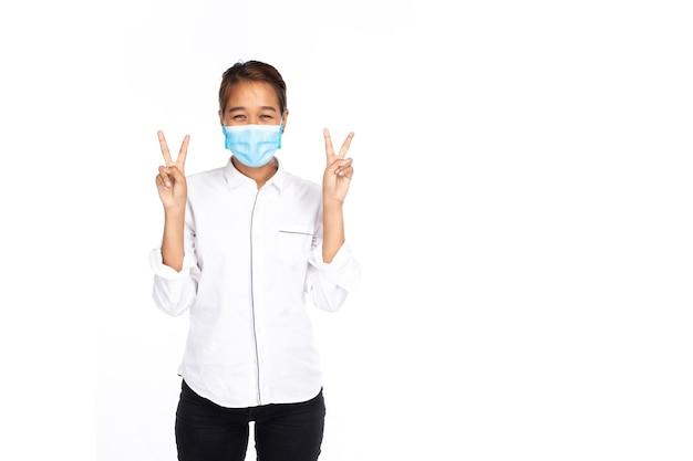 Felice donna asiatica in camicia bianca indossare la maschera per il viso mostra due mani e alza due dita o gesto di vittoria, guarda la fotocamera, ritratto di luce in studio isolato su sfondo bianco, concetto covid-19