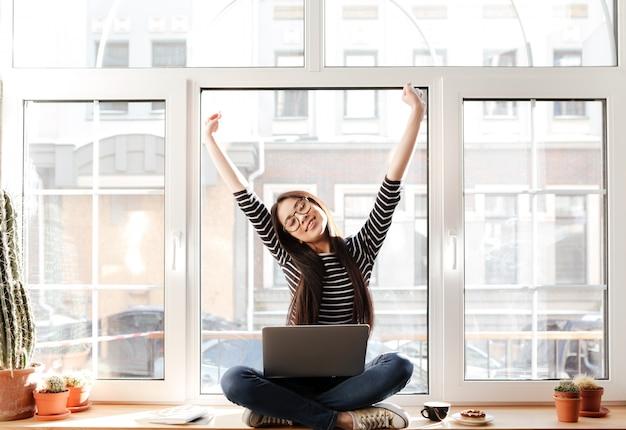 Donna asiatica felice sul davanzale con il computer portatile