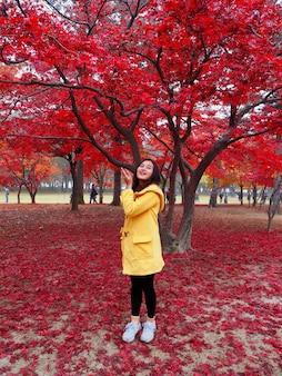 Felice donna asiatica in giacca gialla in piedi nel parco di foglie di acero rosso a nami island colorato autunno