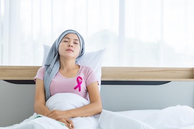 Felice una donna asiatica malata di cancro mammario con nastro rosa che indossa il velo dopo il trattamento alla chemioterapia sedersi fare un pisolino sul letto nella camera da letto a casa, assistenza sanitaria, concetto di medicina