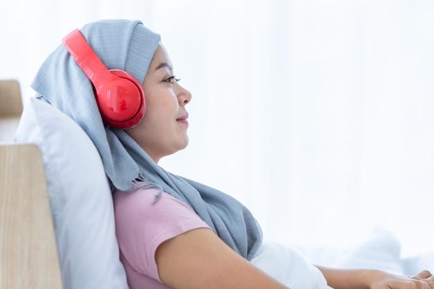 Felice una donna asiatica malata di cancro mammario con nastro rosa che indossa il velo in cuffia sta ascoltando musica dopo il trattamento per la chemioterapia sedersi sul letto nella camera da letto a casa