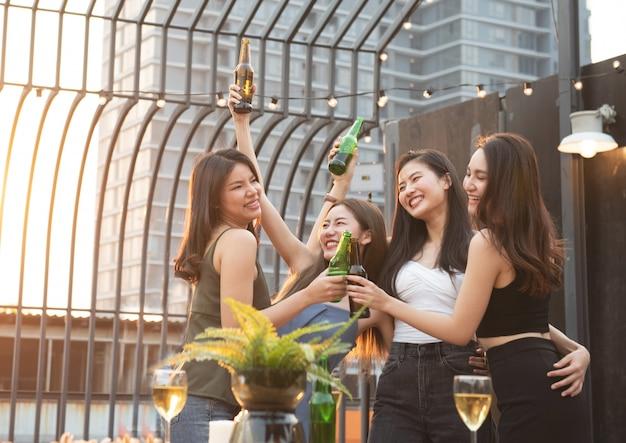 Le donne asiatiche felici fanno festa con la birra in night-club.
