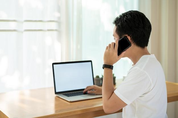 Felice giovane uomo d'affari asiatico che lavora a casa e guardando la telecamera, ha creato un piccolo angolo nel soggiorno per l'home office come il moderno concetto di stile di vita lavorativo.