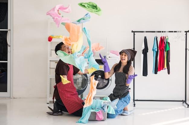 Una giovane coppia asiatica felice lancia un tessuto pulito e colorato per asciugamano da bagno dopo il lavaggio in lavatrice. moglie allegra e marito in servizio domestico che fanno le faccende insieme.