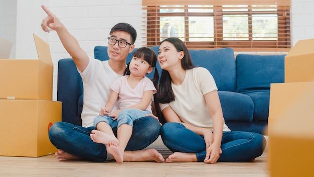 Giovani proprietari di case asiatici felici della famiglia nella nuova casa