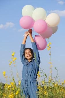 Felice ragazza asiatica al giardino fiorito in estate con un bel cielo.