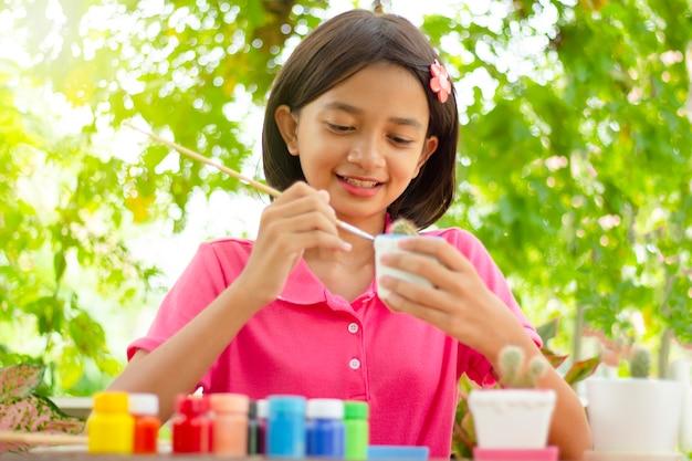 Colore della pittura asiatica felice della giovane ragazza sul vaso del cactus in natura