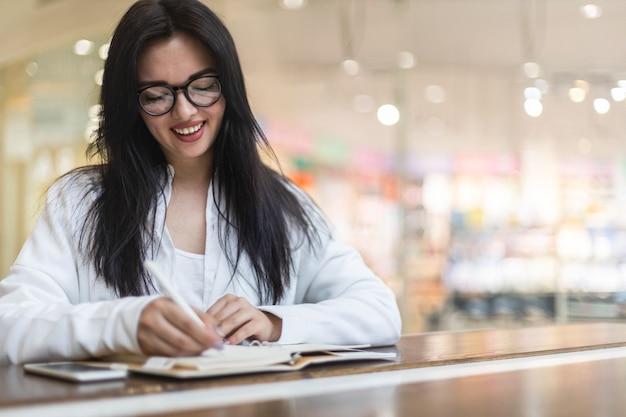 Felice giovane donna asiatica seduta al bar con una tazza di caffè che prende appunti godendosi la pausa