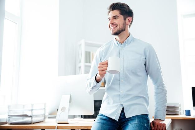 Felice attraente giovane uomo d'affari che beve caffè in ufficio