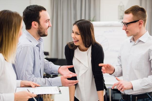 Gruppo di affari attraente felice che sta in un ufficio