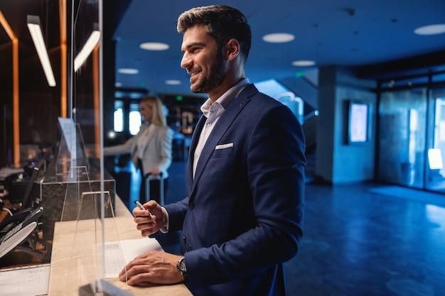 Felice uomo d'affari attraente in piedi a un ricevimento in un hotel di lusso e fare il check-in