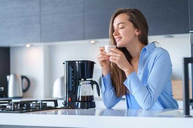 Godere femminile attraente felice dell'aroma fresco del caffè dopo la preparazione del caffè facendo uso della macchinetta del caffè nella cucina a casa. frullatore per caffè ed elettrodomestici da cucina per bevande calde