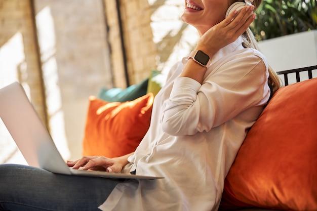 Felice femmina attraente che trascorre il tempo con le cuffie agli ioni nel caffè
