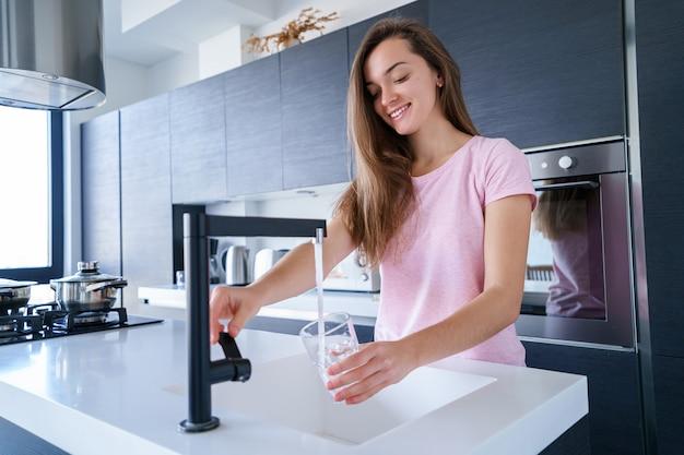 La donna castana allegra attraente felice versa l'acqua purificata filtrata pulita fresca per bere da un rubinetto in un vetro alla cucina a casa. stile di vita sano e dissetarsi
