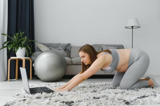 Felice attraente donna incinta in abiti sportivi, facendo esercizi sul tappetino da palestra a casa in soggiorno. salute durante la gravidanza. lezioni di yoga a casa. maternità, gravidanza attiva.