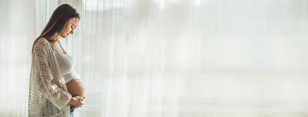 Felice attraente donna incinta in piedi vicino alla finestra e tenendo la pancia. concetti di gravidanza e famiglia
