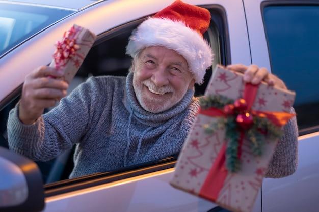 Un uomo anziano felice e attraente in cappello della santa pronto alla consegna a domicilio dei regali di natale con la sua automobile. il vecchio nonno barbuto con un grande sorriso