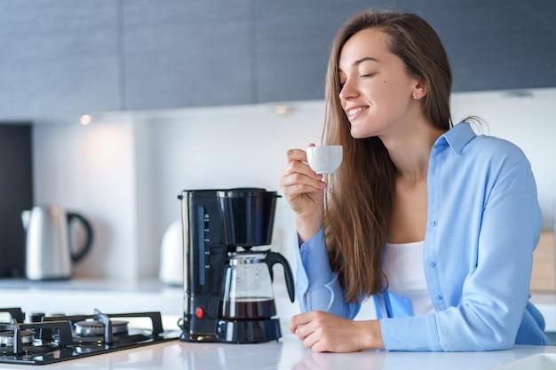 Godere attraente felice della donna dell'aroma fresco del caffè dopo avere fatto caffè facendo uso della macchinetta del caffè nella cucina a casa. frullatore per caffè ed elettrodomestici da cucina per bevande calde