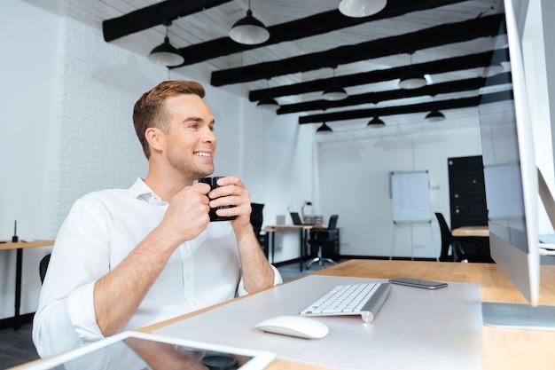 Felice giovane uomo d'affari attraente seduto e bevendo caffè sul posto di lavoro