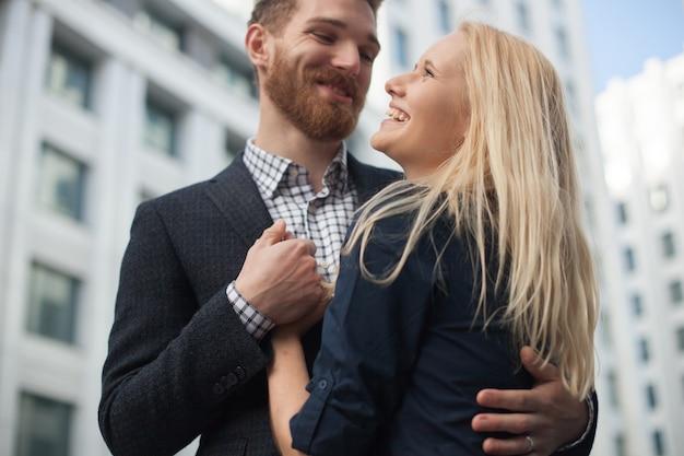 Felice coppia giovane attraente per condividere una bella battuta, ridendo forte, abbracciandosi all'aperto in ambiente urbano