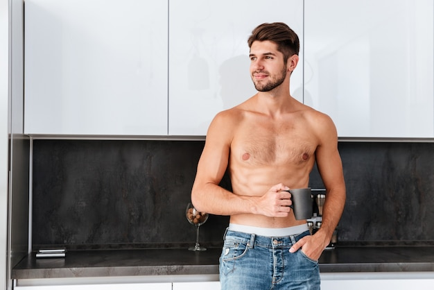 Felice attraente giovane uomo che beve il caffè in cucina a casa