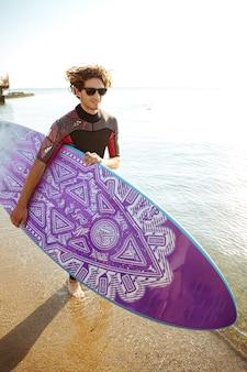 Surfista giovane attraente felice in occhiali da sole con tavola da surf in esecuzione sulla spiaggia