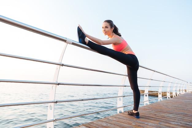 Felice attraente giovane sportiva in piedi e allungando le gambe sul molo