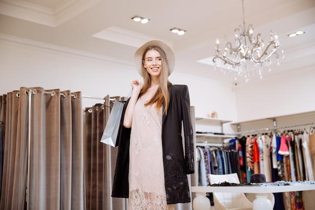 Felice attraente giovane donna con le borse della spesa e in piedi nel negozio di abbigliamento